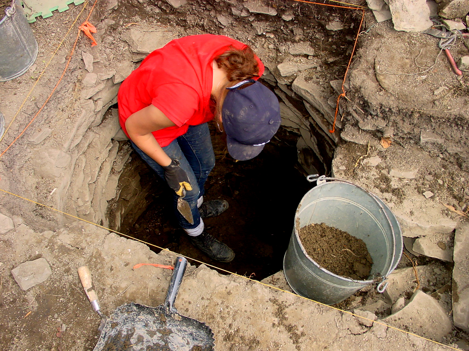 Excavating earth and rocks in well as water begins to seep in from below