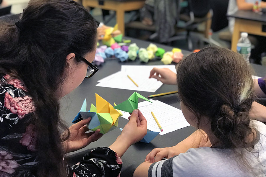 The Girls Math Club, led by Bard students, works on origami designs in the Reem-Kayden Center on Bard's campus. Photo by Bari Bossis '19.
