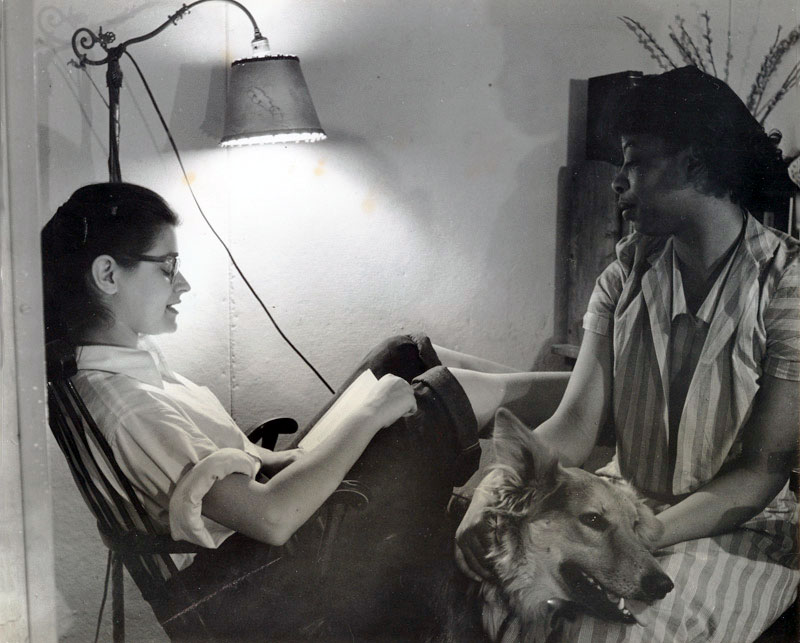 "Cynthia Maris Gross '54 reads to Emerald McKenzie '52, 1952. McKenzie is seen here with her seeing-eye dog, Karen. Gross acted as McKenzie's ""reader"" throughout their shared time at Bard. Photograph by David Brook."