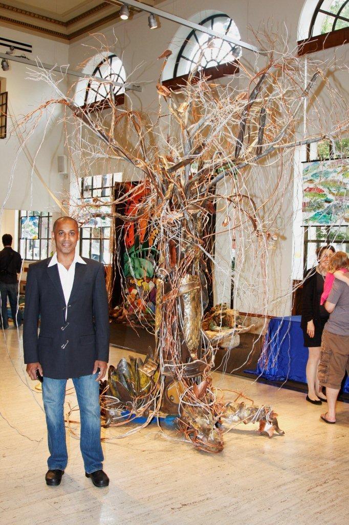 Wilfredo Morel frente a una de sus esculturas