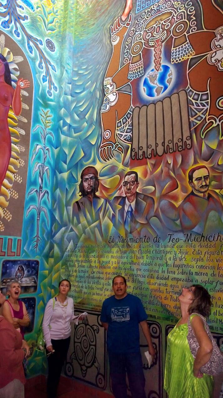 <div>Jes&uacute;s L&oacute;pez Vega (centro) explica su mural a un grupo de expatriados estadounidenses en Ajijic.</div>