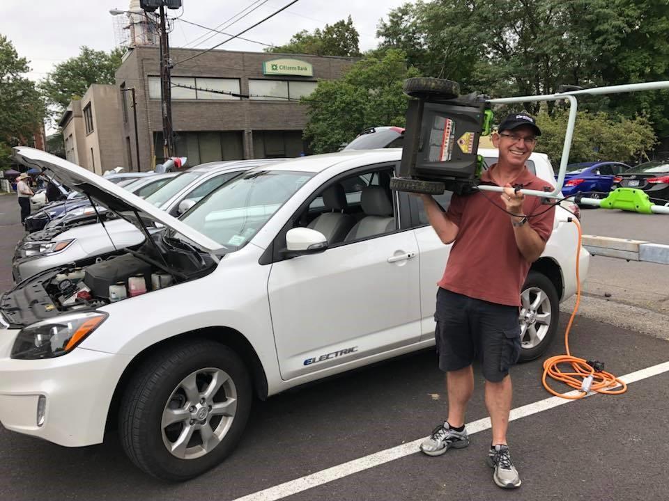 Tom Konrad muestra su cortadora de pasto eléctrica frente a su RAV4 EV at the at 2018 en el evento Maneja Eléctricos de Kingston, NY. Foto de Hugo Jule<br />